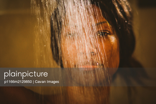 black  sensual Woman in a shower under water - p1166m2129850 by Cavan Images