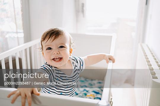 Happy baby boy in crib at home - p300m2293487 by Gerard Moral Casanovas