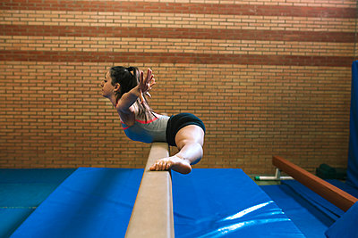 Side view of female gymnast with legs apart and arms outstretched exercising on balance beam against wall at gym - p1166m1576457 by Cavan Images