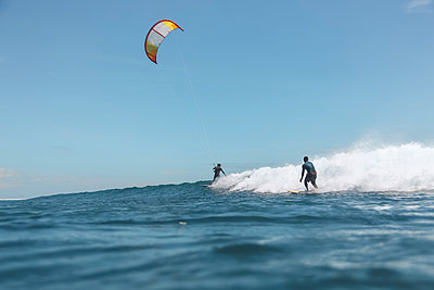 Kite surfer and surfer on the sea - p1166m2111909 by Cavan Images