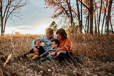 smiling young family snuggling in a field on a fall evening - p1166m2208495 by Cavan Images