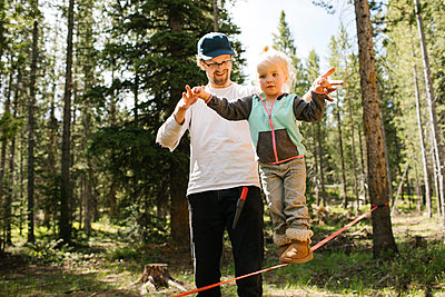 Father assisting daughter (2-3) walking on slackline in forest, Wasatch-Cache National Forest - p1427m2213557 by Jessica Peterson