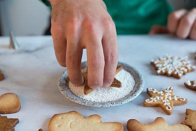 Man's hand decorating Christmas Cookie, close-up - p300m2005386 von skabarcat