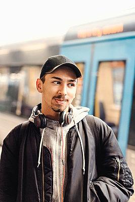 Thoughtful male university student standing at subway station - p426m1003756f by Maskot