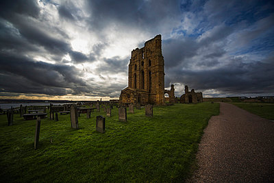 Ruins of the Tynemouth Priory and an old cemetery at sunset; Tynemouth, Tyne and Wear, England - p442m837736f by John Short