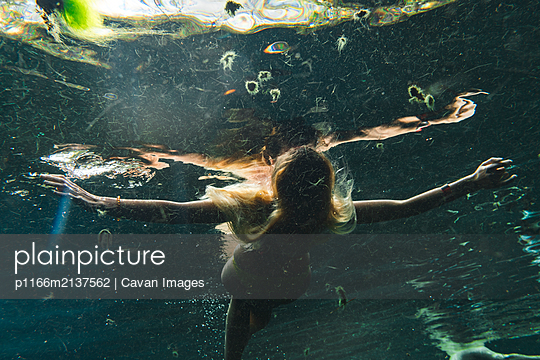 Woman floating close to water surface while enjoying underwater bath - p1166m2137562 by Cavan Images