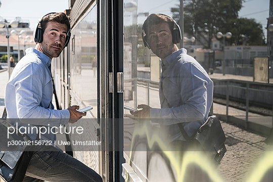 Young man with headphones and smartphone entering a train - p300m2156722 by Uwe Umstätter