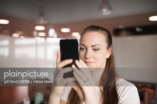 Young woman photographing with cell phone - p312m2138786 by Viktor Holm