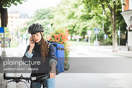Food delivery woman talking on mobile phone at street in city - p426m2145437 by Maskot