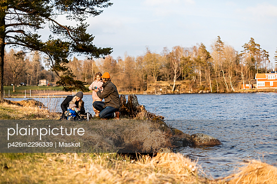 Mid adult man and woman with children by lake at park - p426m2296339 by Maskot