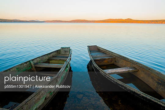 Two rowboats on lake at sunset - p555m1301947 by Aleksander Rubtsov