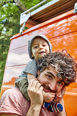 Father gives baby boy a piggyback on camping vacation - p1146m2196037 by Stephanie Uhlenbrock