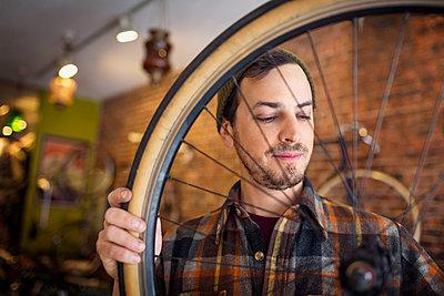 Man looking at bicycle wheel while standing in workshop - p1166m1096017f by Cavan Images