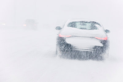 Car driving on highway in blizzard - p1418m1572032 by Jan Håkan Dahlström