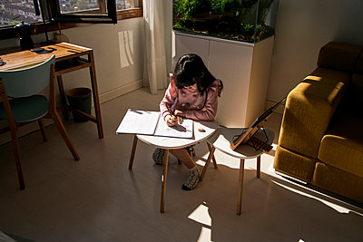 Girl doing homework in the living room - p300m2188503 by Eloisa Ramos