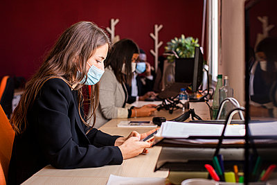 Young businesswoman in protective face mask text messaging through smart phone at desk in office during pandemic - p300m2226053 by DREAMSTOCK1982