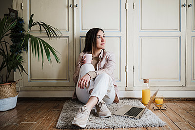 Thoughtful businesswoman looking away while sitting on rug at home - p300m2274547 by Eva Blanco