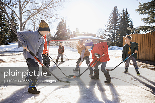 Boys playing ice hockey on sunny, snowy driveway