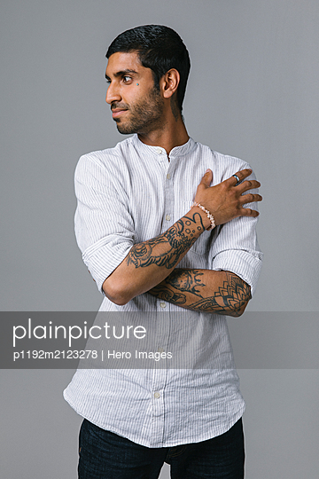 Portrait confident, cool young man with tattoos - p1192m2123278 by Hero Images