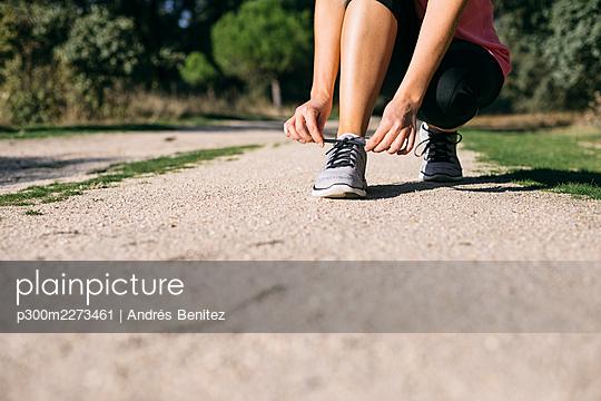 Woman tying shoelace on footpath - p300m2273461 by Andrés Benitez