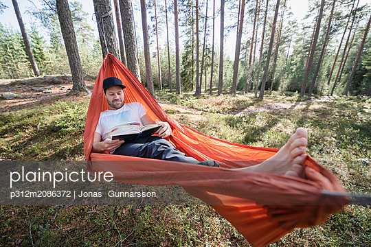 Man reading book in hammock in forest - p312m2086372 by Jonas  Gunnarsson