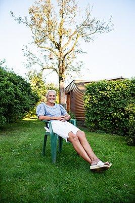 Senior woman in her garden - p1093m2192928 by Sven Hagolani