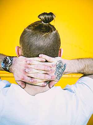Man with pigtail and tattoo on his hand - p1267m2263389 by Jörg Meier