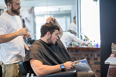 Young man at barber's shop discussing with hairdresser - p300m1113267f by zerocreatives