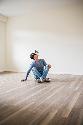 Man in empty apartment wearing VR glasses - p300m1459861 by Uwe Umstätter