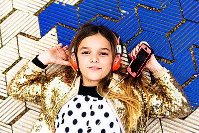 Portrait of girl wearing golden sequin jacket listening music with headphones and smartphone - p300m2102989 von Eloisa Ramos