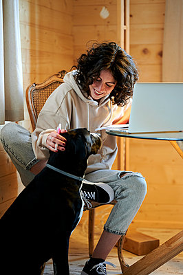 Smiling woman stroking dog at home - p300m2282143 by Kiko Jimenez