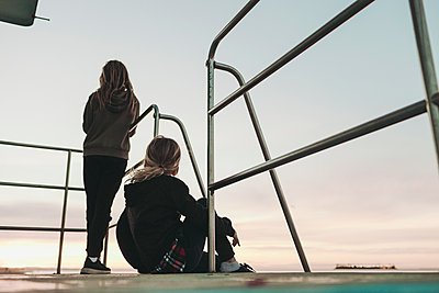 Two girls sit on a lifeguard station at dawn looking out to the ocean; Long Beach, California, United States of America - p442m2016265 by Melody Davis