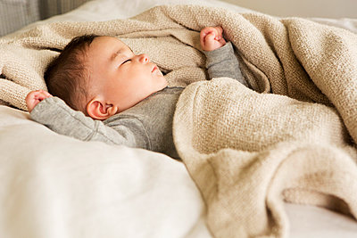 Mixed race baby sleeping in bed - p555m1411807 by Lucy von Held