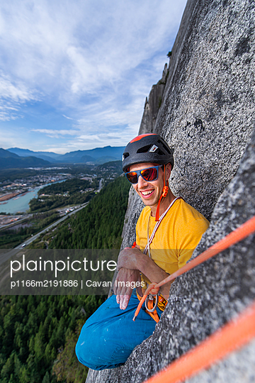 Man sitting funny position while rock climbing with helmet sunglasses - p1166m2191886 by Cavan Images