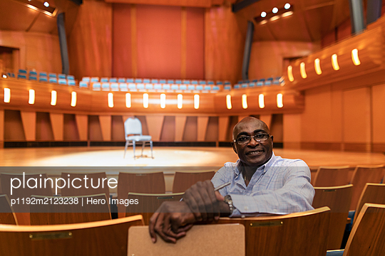 Portrait confident male event coordinator with clipboard in auditorium - p1192m2123238 by Hero Images
