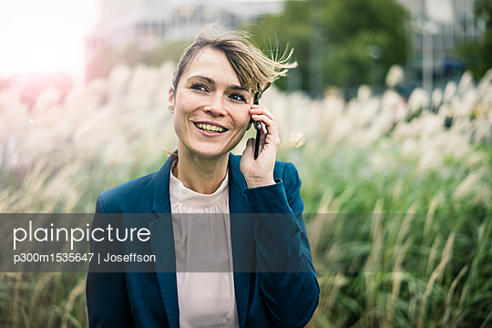 Smiling businesswoman on cell phone outdoors - p300m1535647 by Joseffson