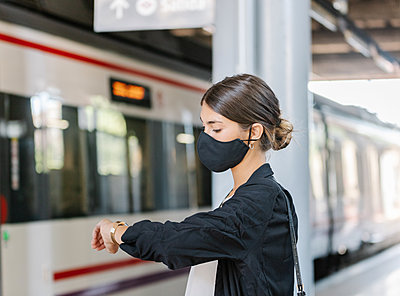 Female entrepreneur checking time on train station - p1166m2214599 by Cavan Images