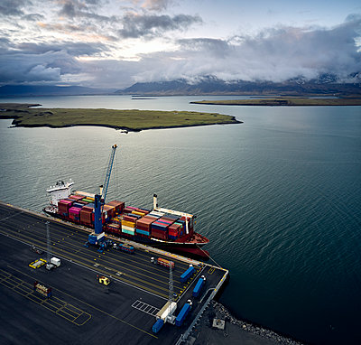Sea wharf with cargo ship under clouds - p1166m2261874 by Cavan Images
