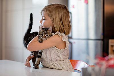 Mädchen mit Katze am Küchentisch - p1212m1091968 von harry + lidy