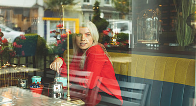 Woman looking through window while stirring coffee - p1315m2056345 by Wavebreak