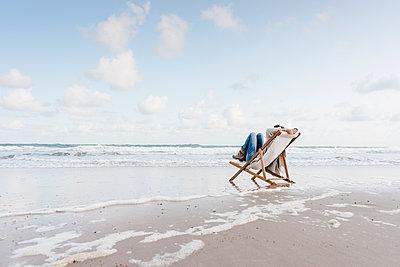 Woman sitting on deckchair on the beach - p300m1499622 by Kniel Synnatzschke
