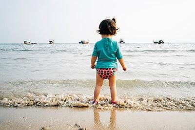 Thailand, Koh Lanta, back view of baby girl wearing UV protection shirt standing at seashore - p300m2070239 von Gemma Ferrando