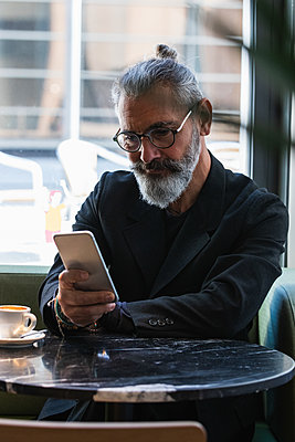 Businessman using mobile phone while sitting at cafe - p300m2276318 by NOVELLIMAGE