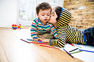 Boy kissing baby brother while lying on floor drawing - p429m1418476 by Bonfanti Diego