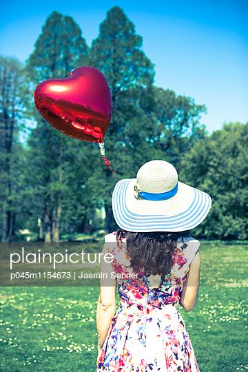 Frau im Park mit Herzluftballon - p045m1154673 von Jasmin Sander