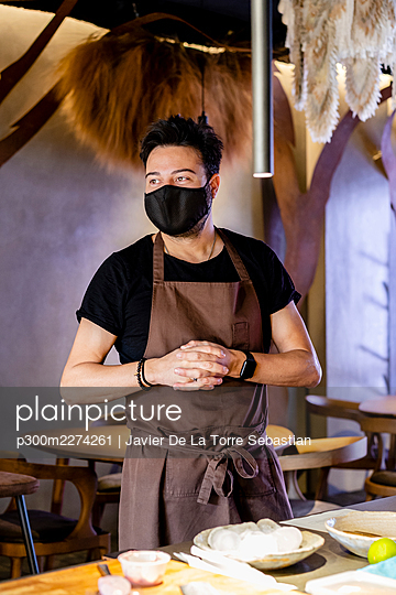 Mature chef with protective face mask in apron looking away while standing at restaurant - p300m2274261 by Javier De La Torre Sebastian