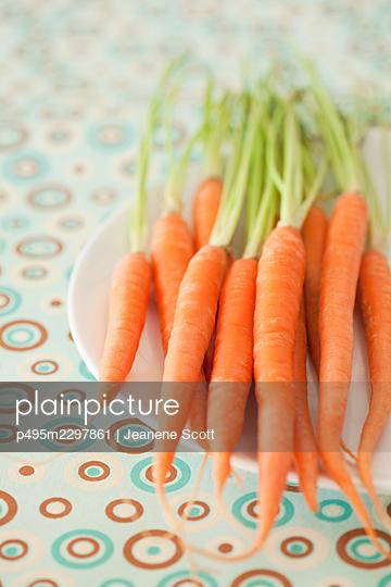 Organic carrots on a white plate - p495m2297861 by Jeanene Scott