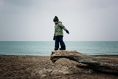 young boy aged 6 playing on log at the beach in winter - p1166m2090634 by Cavan Images
