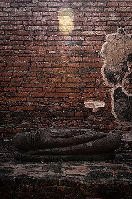 Beschädigter Buddha vor Backsteinwand - p1273m1496186 von melanka