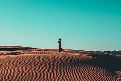 Young woman with windswept hair standing in desert landscape - p300m2004446 by Oriol Castelló Arroyo